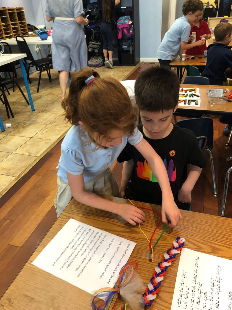 Children practice braiding yarn at a table with Havdallah supplies.