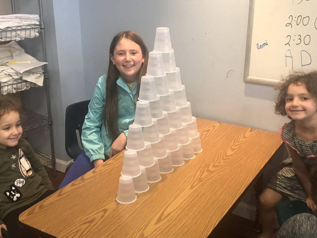 Three kiddos sitting next to a tall pyramid of plastic cups.