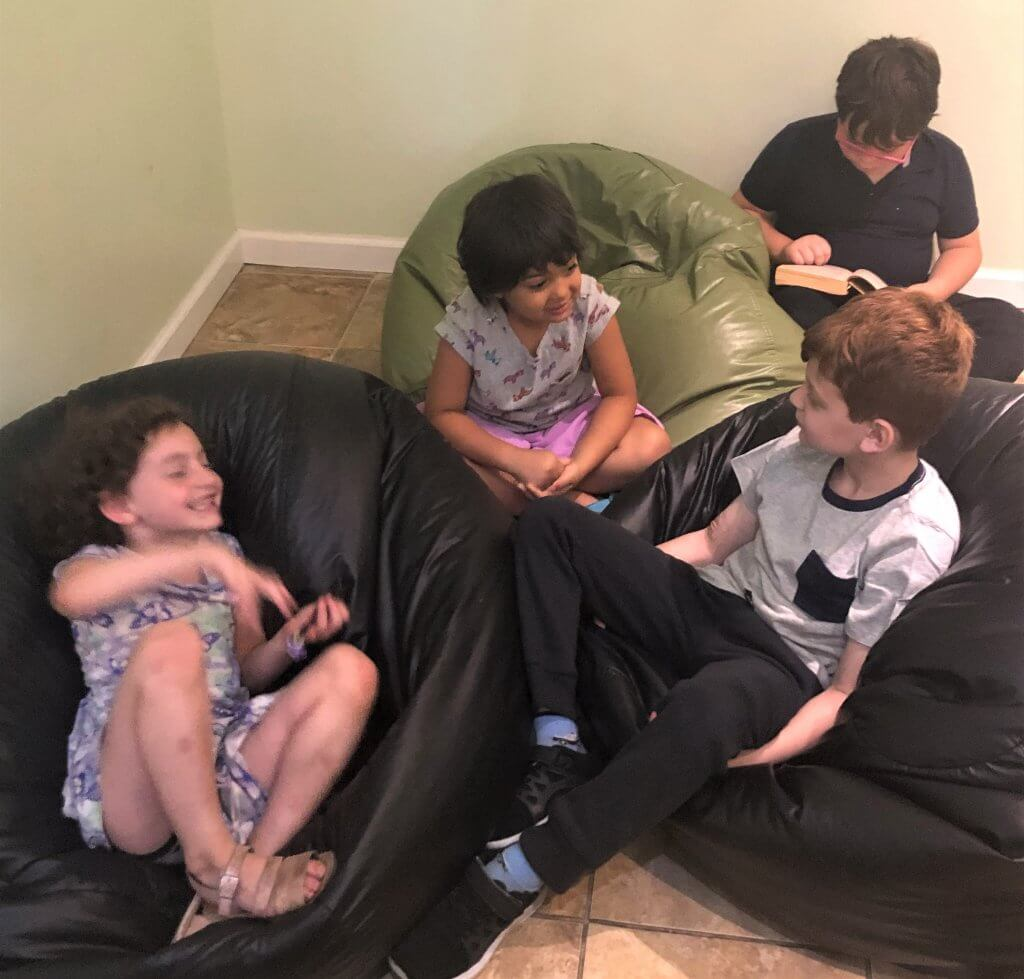 Four kids in beanbags telling spooky stories.