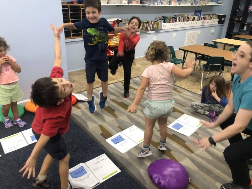 Kiddos jumping joyfully during Tefilah: Prayer, Music, and Movement.