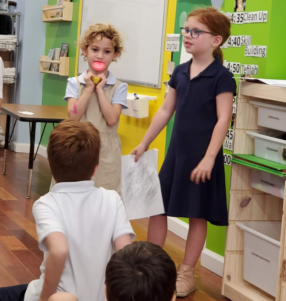 A first grader and a kindergartner present their evidence of a scribbled on paper.
