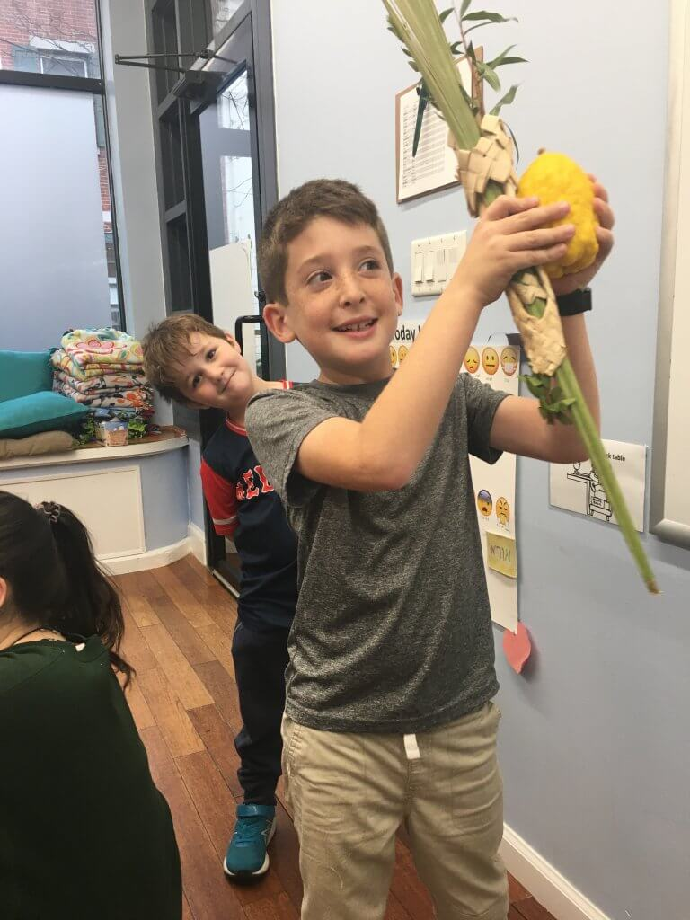 A 2nd grader shakes lulav while a 1st grade friend photobombs.