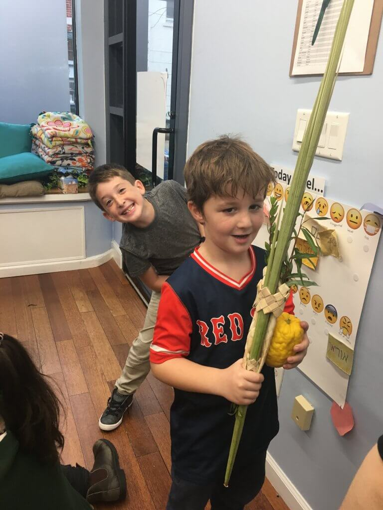 A 1st grader shakes lulav while a 2nd grade friend photobombs.