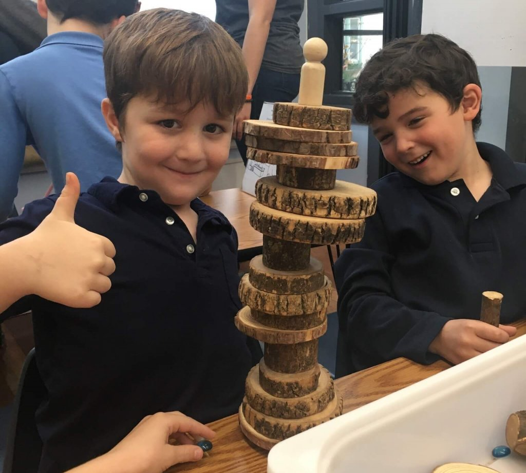 Two students show off the tower they built out of natural materials.