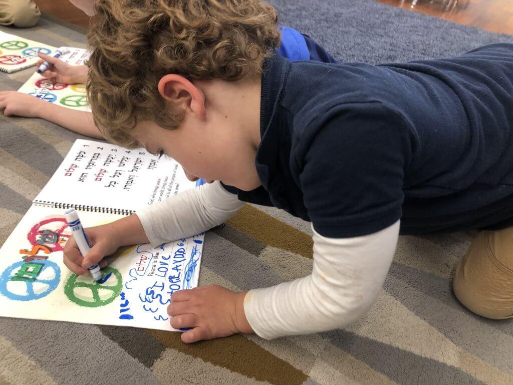 Kindergarten student reflecting on peace in his siddur (prayer book).