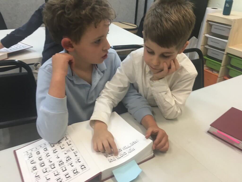 Two students working on mastering a tefilah (prayer) together.