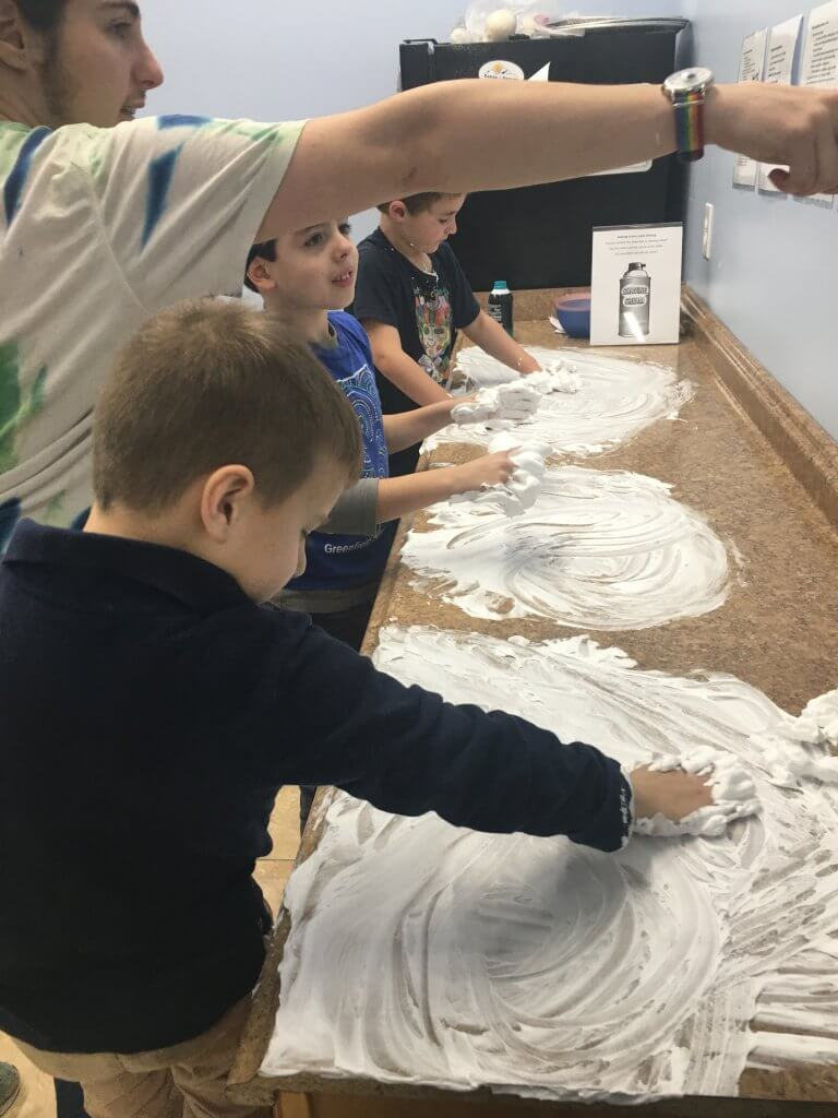 Practicing writing Hebrew letters in shaving cream.