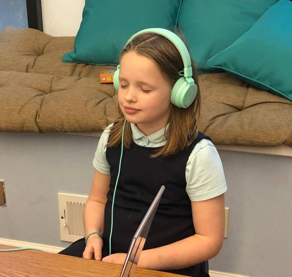 Second grade student peacefully meditating.