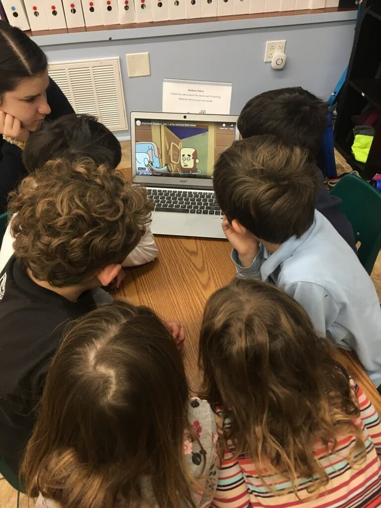 Isabella and a group of students crowd around a computer to watch an animated version of the story from our text.