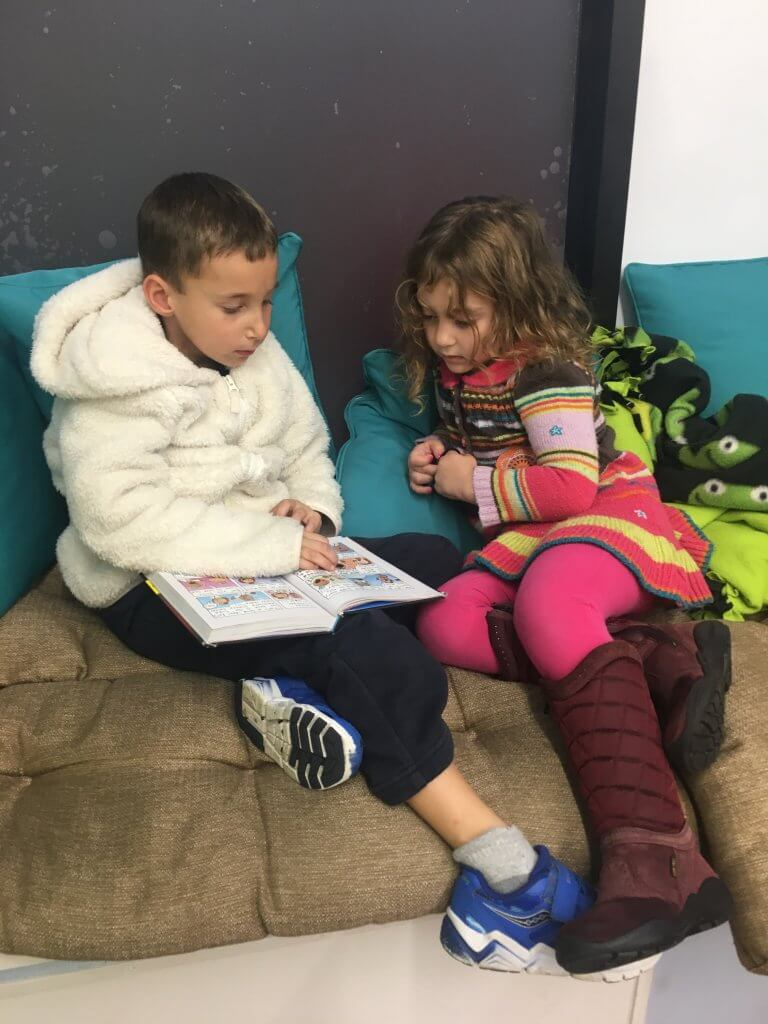 A 1st grader cozies up with a PreK kid to read on the windowsill.