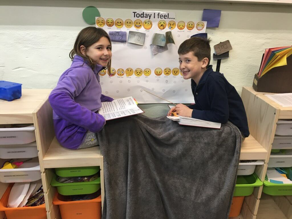 Two nitzanim (2nd-4th grade) kiddos get cozy to practice tefilah (prayer) together.