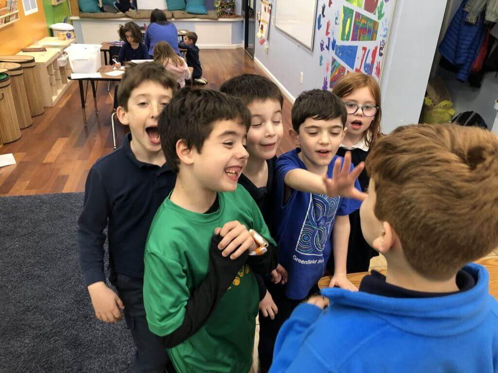 A group of students laugh through a drama activity together.