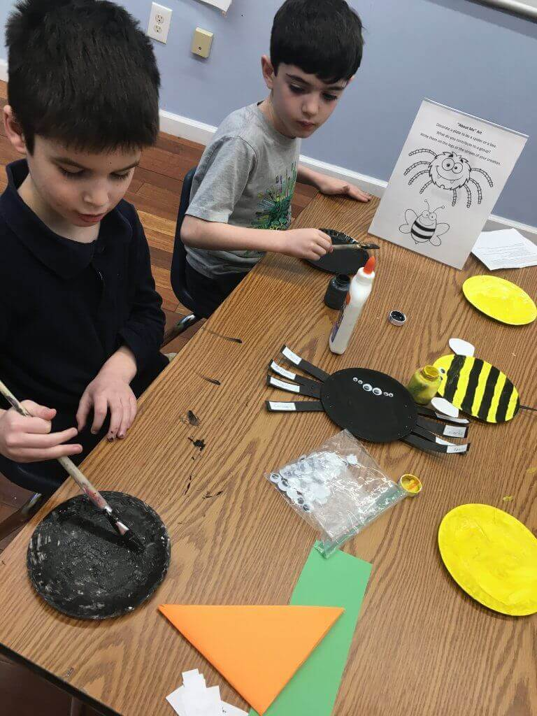 Two first grade students make spider crafts about what makes them great.