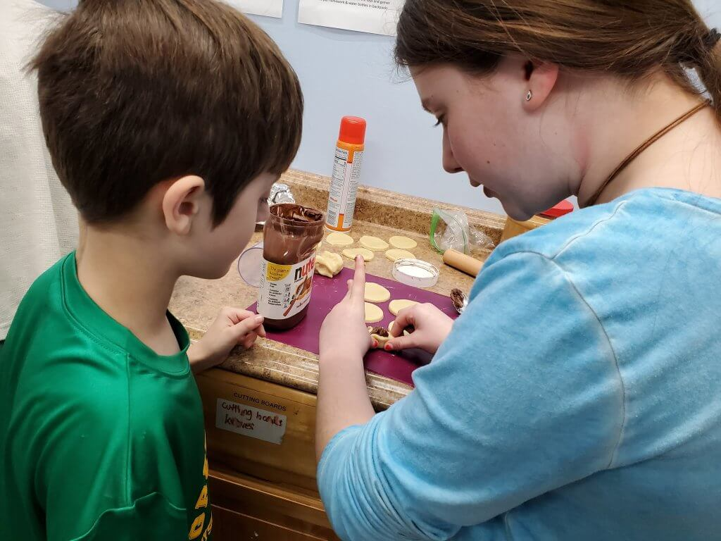 A BMitzvah student helps a 3rd grader make Hamantaschen.