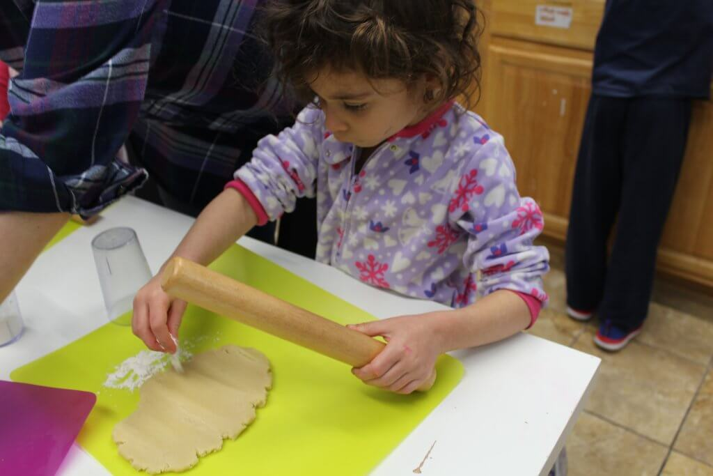 A pre-K kiddo rolls out dough for Hamantaschen.