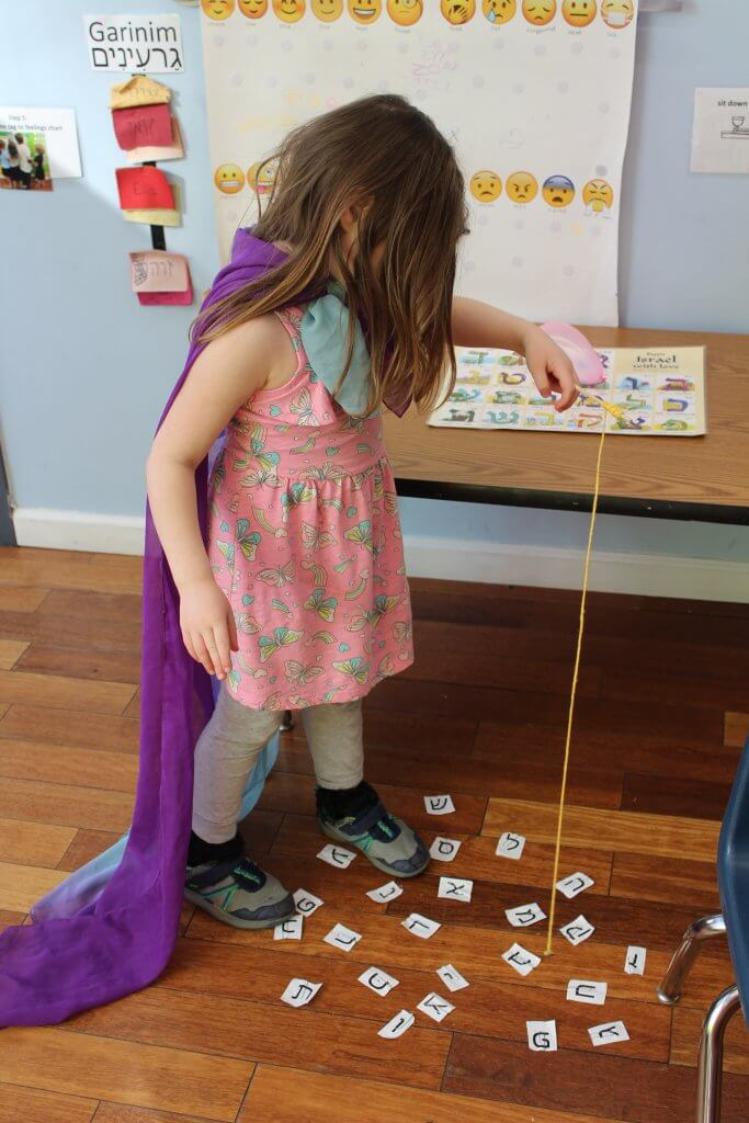 A pre-K student goes fishing for Hebrew letters.