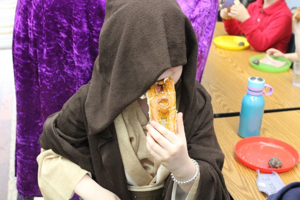A jedi eating a soft pretzel at our Purim seuda.