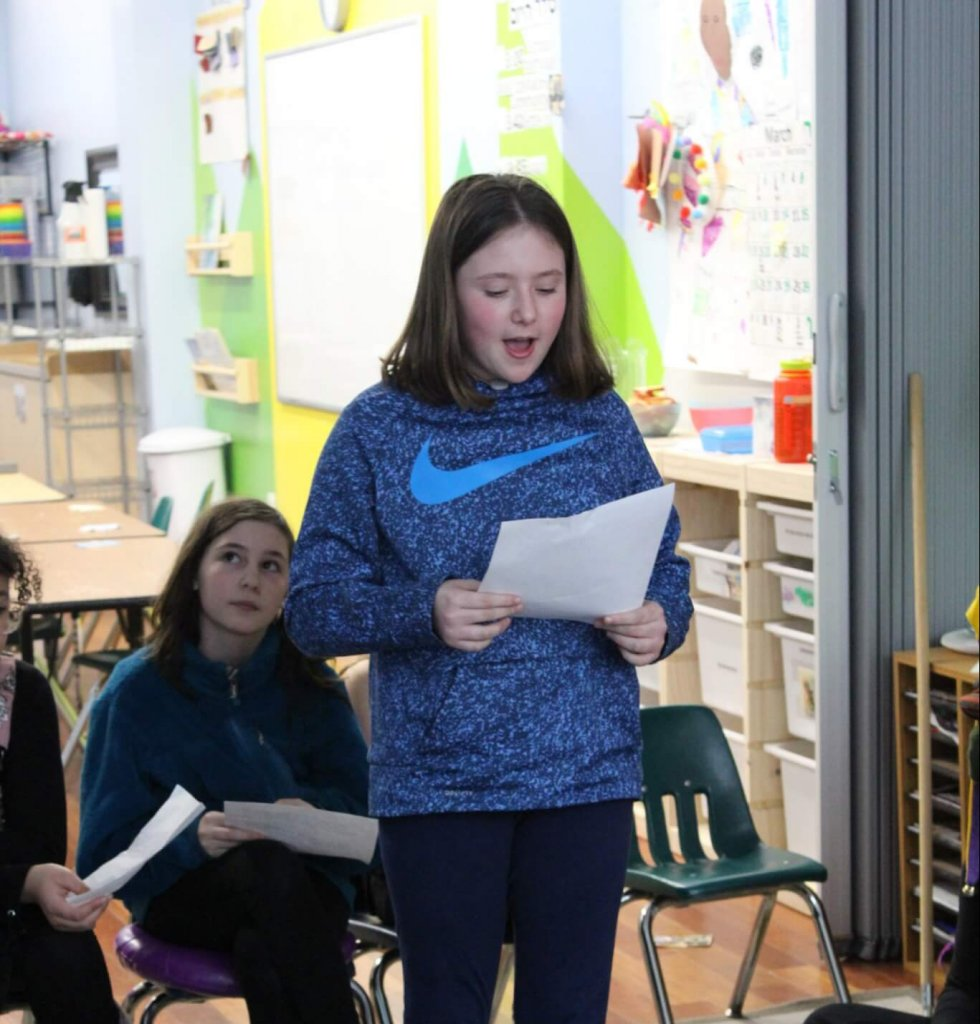 A BMitzvah student reading a sentence of Megilat Esther.