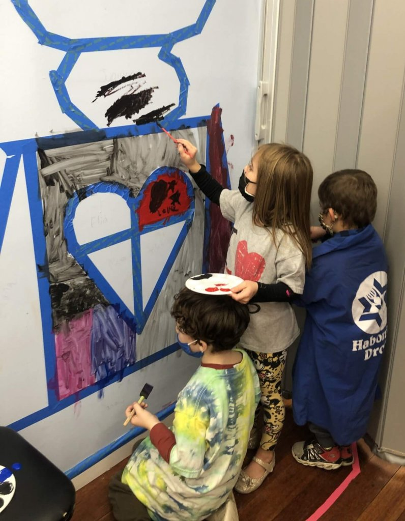 PreK, K, and 1st graders paint on their brit