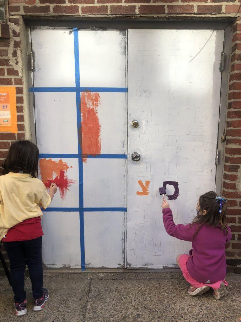 Two kindergarteners paint the doors to Makom on Ionic Street.