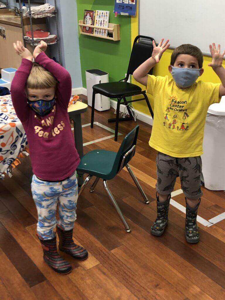 Two preK kiddos singing and dancing to tefilah