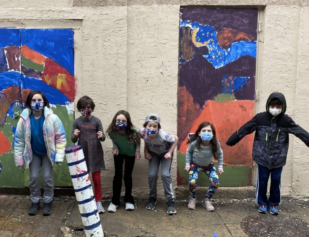 Third and Forth graders jumping in front of their outdoor paintings.