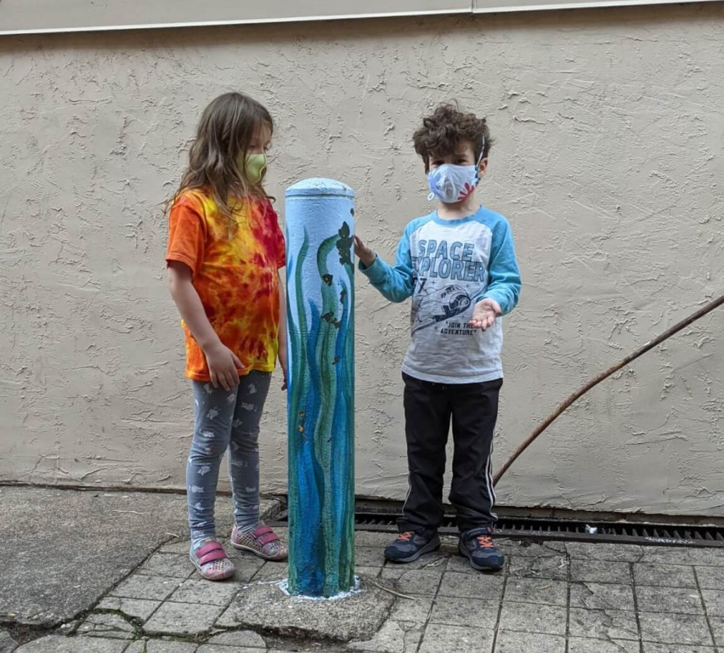 Two first graders standing outside next to a pole
